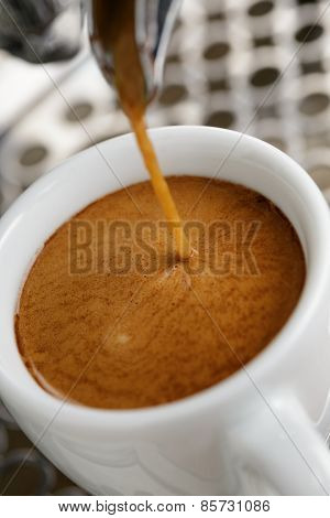 espresso pouring from professional coffee machine into white cup