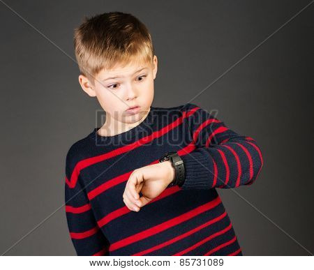 Schoolboy looking pointing at his watch and worried that he is late.