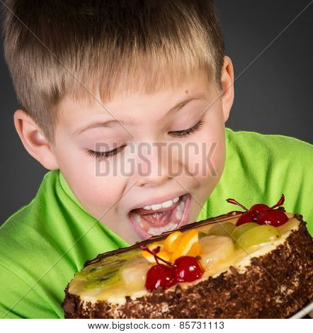 Closeup portrait of cute funny boy staring longingly at cake. Child trying to bite a cake.