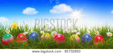 Colorful Easter Eggs On Green Meadow.