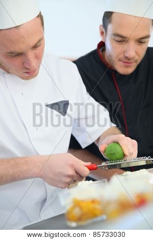 Young cook preparing dessert with chef behind him