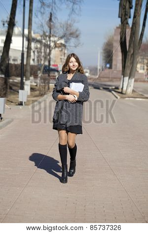 Young beautiful girl in a gray coat walking down the street