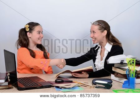 Schoolmarm congratulated apprentice, shaking her hand with successful execution of tasks
