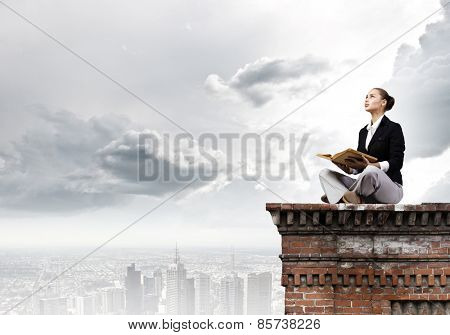 Young attractive businesswoman sitting on roof of building and reading book