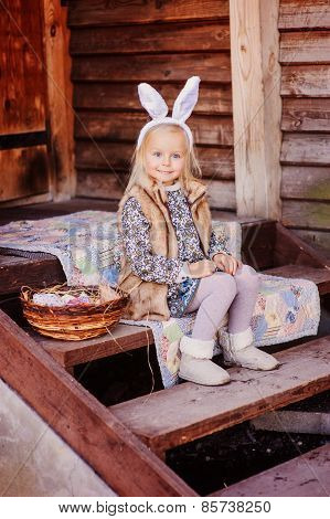 happy child girl wearing bunny ears for easter at country house