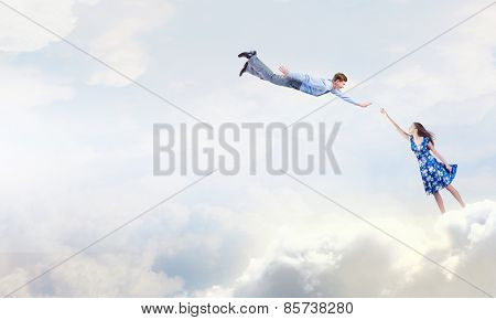 Young elegant woman trying to reach man