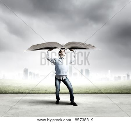 Young man holding huge book above head