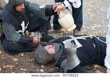 ZAGREB, CROATIA - OCTOBER 07, 2012: Knight giving water to another injured knight after the battle at