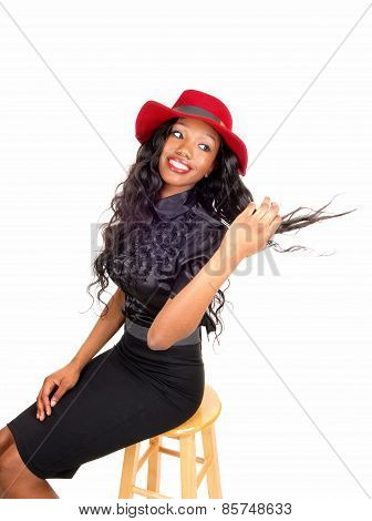 Black Woman With Red Hat Sitting On Chair.