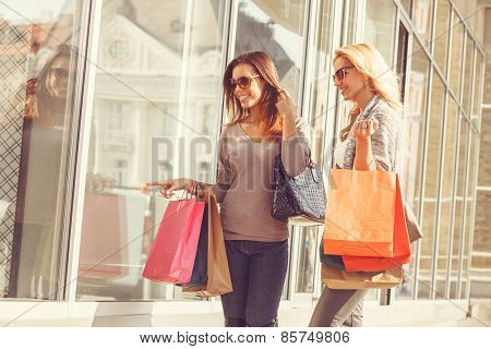 Two Young Women Looking In Showcase