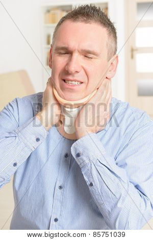 Man with a surgical cervical collar suffering from neck pain