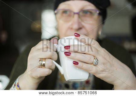 hands of real senior woman with white cup