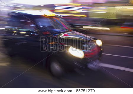 Abstract blurry image of a London taxi cab driving on a street.