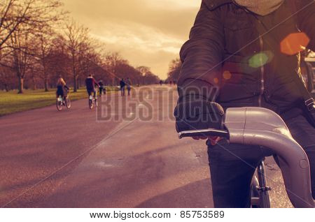 closeup of a young caucasian man very sheltered riding a bicycle in Hyde Park in winter in London, United Kingdom, filtered and with a lens flare