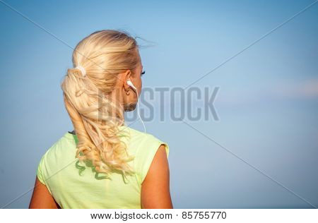 Attractive sporty young woman standing on the beach taking a break from exercising and listening to music with her mp4 player and head phones against a blue sky