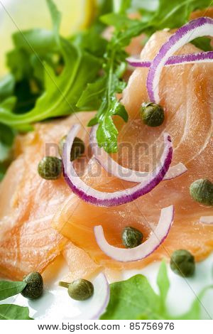 Smoked salmon with red onion, capers and arugula or rocket.