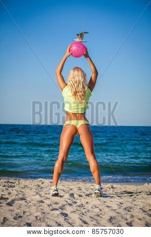 Beach woman in bikini holding a volleyball