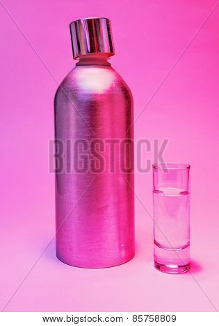 Aluminum bottle and a glass of vodka in pink purple light