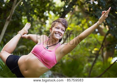 Woman practicing yoga outdoors - dancers pose, natarajasana
