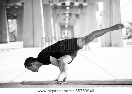 Man practicing advanced yoga in a urban background