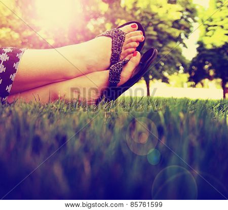 pretty feet on grass at sunset with nails painted and sandals on toned with a retro vintage instagram filter