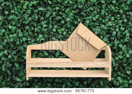Brown Envelope In Letter Box On Turf Background