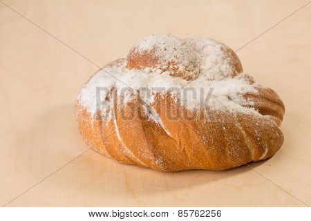 twisted bread top with sugar icing on wooden board