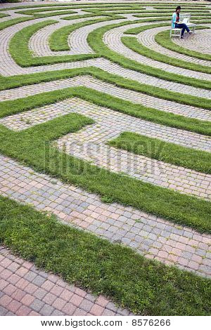 Woman Using Laptop in a Cobblestone Maze