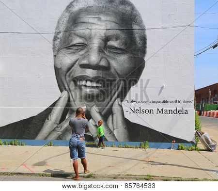 Unidentified family taken picture in the front of Nelson Mandela mural in Brooklyn