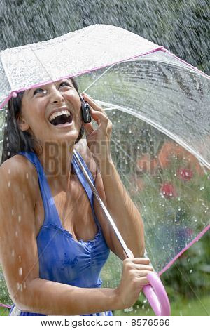 Young Woman Using a Cellphone and Umbrella in Rain