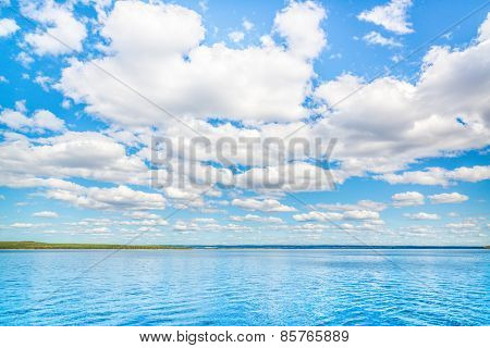 summer photo of lake and sky with small clouds
