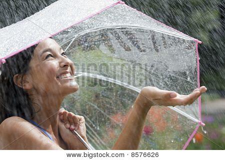 Young Woman Using an Umbrella in Rain
