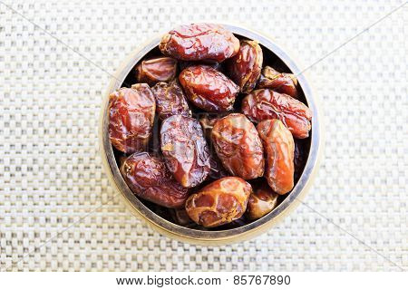 Sultana variety dates kept in a bowl under a plain background
