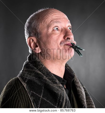 Senior Man Keeping Silence With Closed Mouth By Clothespin