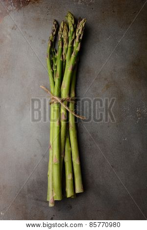 A single bunch of Asparagus tied with twine on a metal cooking sheet. Vertical format shot from a high angle.