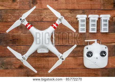 Fort Collins, CO, USA - March 17, 2015:  DJI Phantom 2 with a radio controller and spare LiPo batteries, top view against rustic wooden wood table