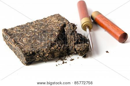 black pu-erh chinese tea with special knife on a white background