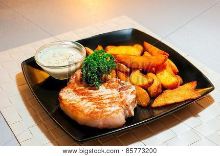 Delicious Pork Steak With Garnish On A Black Plate