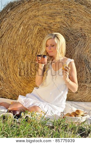 Happy woman posing with bread, milk and hay