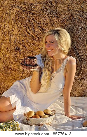 Happy woman posing with bread, coffee cup and hay