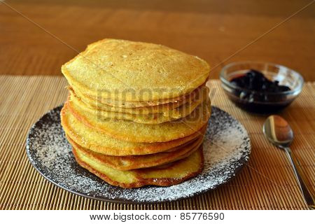 Stack of sweet homemade pancakes with jam and icing sugar