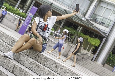 KUALA LUMPUR - March 01, 2015: Undefined tourists taking pictures on Suria KLCC in Petronas Twin Towers background on March 01, 2015 in Kuala Lumpur.