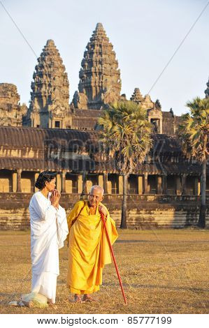 Two Unidentified Buddhist Female Monks Dressed In Orange And White Togas At Angkor Wat Temple.