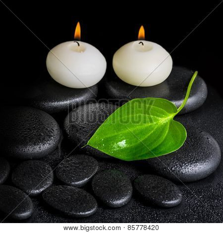 Spa Concept Of Two White Candles And Green Leaf On Black Zen Stones Background With Dew, Closeup