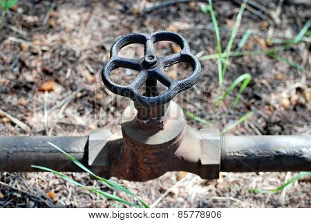 water pipe with a valve lies on the ground