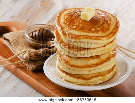 Stack Of Small Pancakes With Maple Syrup On  A Wooden Table