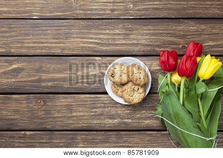 Tulips And Cookies On A Wooden Table.