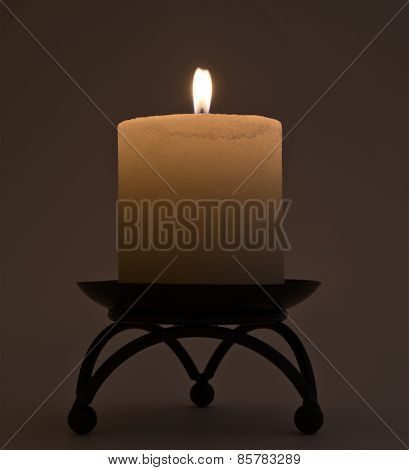 Burning candle on the metal stand