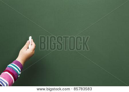 Child writing in blackboard