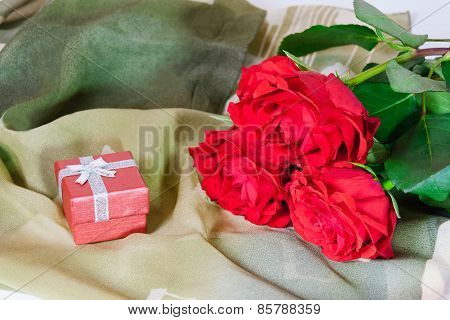 Red Gift Box And Three Red Roses On A Green  Silk Scarf
